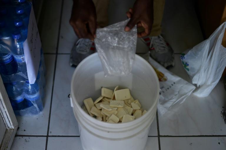 AFP/Archives / HECTOR RETAMAL Un employé d'hôtel rassemble des savons usagés, le 6 juin 2017 à Port-au-Prince